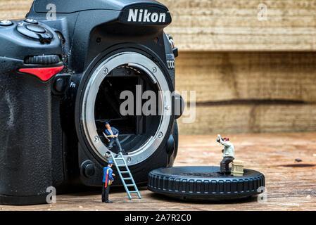 Kamera Sensor Reinigung von Figuren, Miniatur, miniatur Menschen Reinigung Kamera und Obst pflücken, Szenen des Lebens, miniatur Szen - Stockfoto