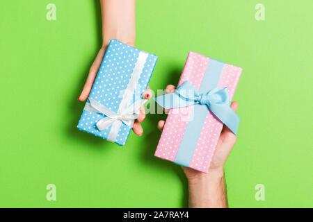 Blick von oben auf eine Frau und einen Mann den Austausch von Geschenken auf farbigen Hintergrund. Paar Geschenke zu einander. Nahaufnahme der Überraschung für Urlaub con - Stockfoto