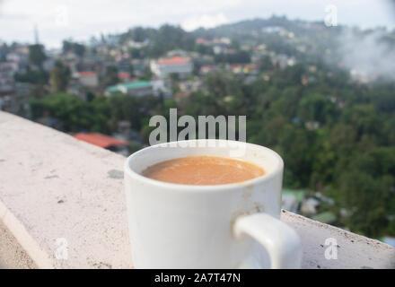 Eine Tasse Darjeeling Milch Tee am Morgen für Entspannung mit einem schönen Blick auf die Stadt Kalimpong, West Bengal, Indien. - Stockfoto