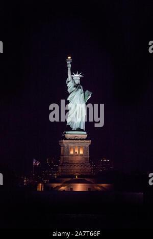 Freiheitsstatue bei Nacht von der Staten Island Ferry, New York City, Vereinigte Staaten von Amerika fotografiert. - Stockfoto
