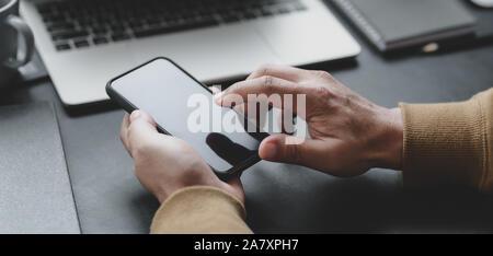 7/8 shot professioneller Geschäftsmann berühren Smartphone in seinen dunklen Luxus Büro Zimmer - Stockfoto