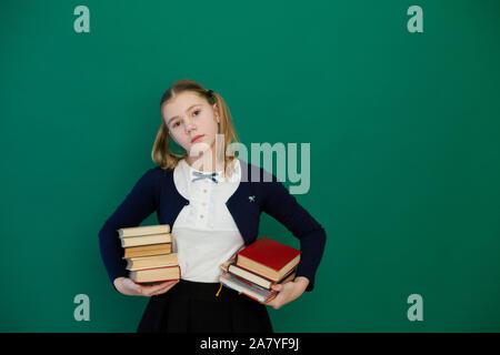 Schulmädchen mit Büchern in der Klasse, die am grünen Brett - Stockfoto