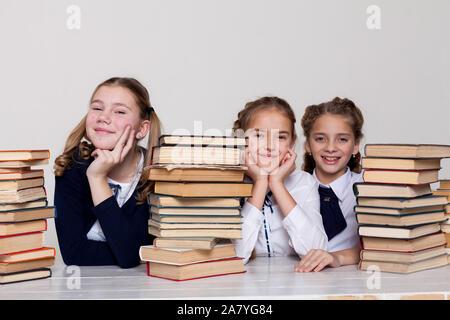 Drei schulmädchen Mädchen mit Büchern in der Bibliothek in der Klasse an der Rezeption - Stockfoto