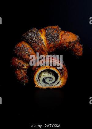 Süße Brötchen mit Mohn auf schwarzem Hintergrund. Hausgemachte roll Horn mit Mohn. - Stockfoto