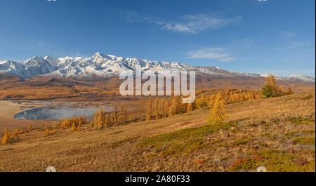 Erstaunlich herbst Panorama mit Berge mit Schnee und Wald bedeckt, der goldene Lärchen, einem wunderschönen See, Nebel und Reflexionen auf dem Hintergrund des blauen Himmels - Stockfoto