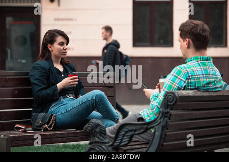 Lächelndes Paar sitzt auf der Bank, die miteinander sprechen, trinken Kaffee - Stockfoto
