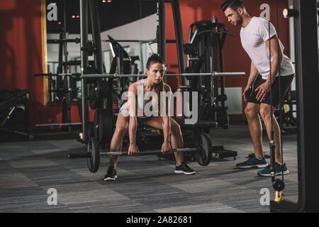 Stattliche trainer Betreuung attraktive Sportlerin anheben Barbell - Stockfoto