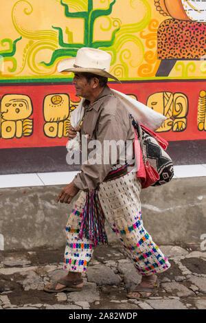 Ein Maya Bauer in traditioneller Kleidung Spaziergänge entlang einer Straße vor einer bemalten Wand in San Pedro La Laguna am Lago Atitlan in Guatemala. - Stockfoto