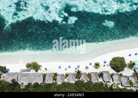 Luftaufnahme von tropischen weißen Strand mit blauen Schirme, Coral Reef und Palmen. Abstrakte drone Schuß von oben. Reisen und Urlaub Konzept.