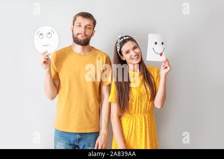 Glückliches Paar holding Blatt Papier mit gezogenen Emoticons auf grauem Hintergrund - Stockfoto