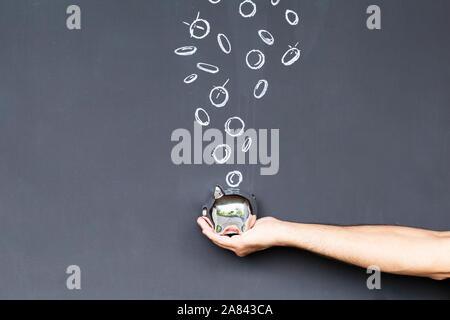 Konzept der Geld sparen mit einem silberfarbenen Sparschwein in der Hand vor einer Tafel mit Hand gezeichnet Münzen statt - Stockfoto