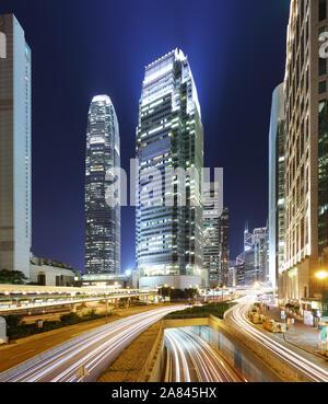 Moderne Bürogebäude im Zentrum von Hong Kong bei Nacht mit Verkehr