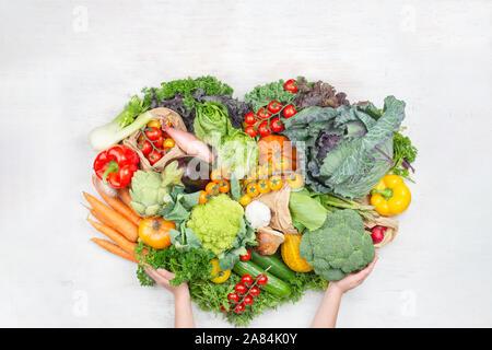 Gesund einkaufen. Child's Hände, die Rainbow Gemüse in einer Form des Herzens auf weissem Holztisch Tomaten Kohl Grüns Möhren Brokkoli, Ansicht von oben, auf weissem Holztisch, selektiver Fokus - Stockfoto