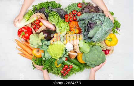 Das gesunde Essen. Child's Hände, die Rainbow Gemüse in einer Form des Herzens auf weissem Holztisch Tomaten Kohl Grüns Möhren Brokkoli, Ansicht von oben, auf weissem Holztisch, selektiver Fokus - Stockfoto