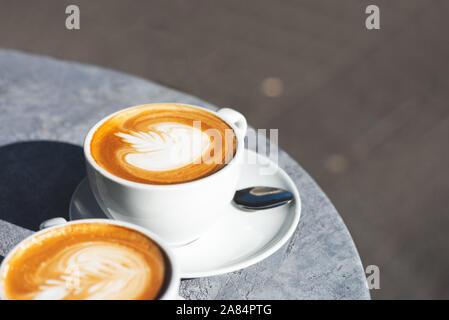 Zwei Tassen flache weiße Kaffee im Café, in der schönen, sonnigen Tag, Schatten auf dem Tisch Stockfoto