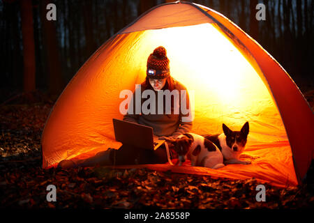 Frau mit Hund mit Laptop in glühenden Zelt - Stockfoto