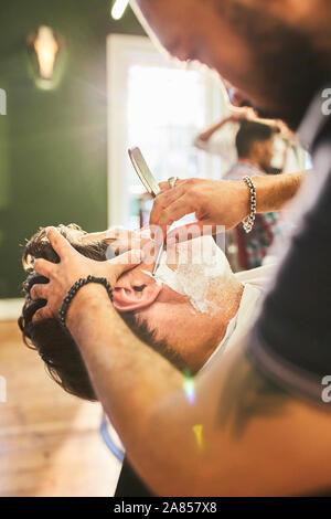 Männliche Friseur eine Rasur in barbershop Kunde - Stockfoto