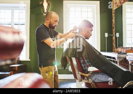 Fokussierte männliche Friseur dem Kunden einen Haarschnitt in Barbershop - Stockfoto