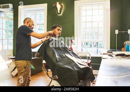 Männliche Friseur dem Kunden einen Haarschnitt in Barbershop - Stockfoto