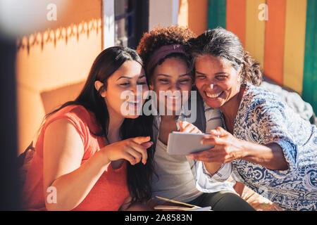 Glückliche Mutter und Töchter nehmen selfie mit smart phone - Stockfoto