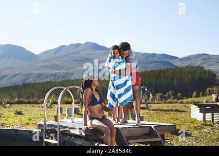 Glücklich, liebevolle Familie an entfernten, sonnig, im Sommer am Pool - Stockfoto