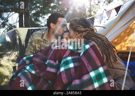 Glücklich, liebevolle Eltern küssen Sohn, entspannen im Campingplatz - Stockfoto