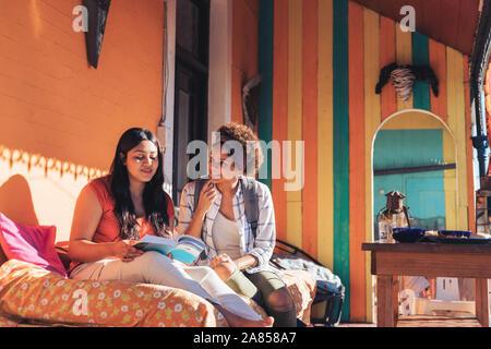 Junge Frauen Freunde lesen Buch über sonnige Terrasse - Stockfoto