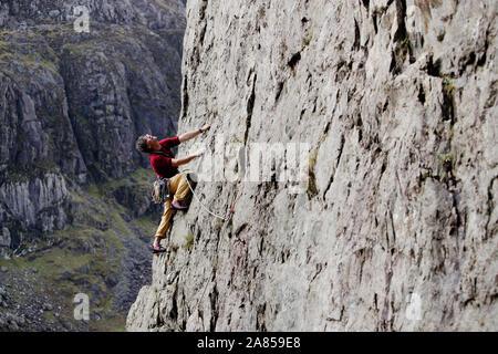 Männliche Kletterer Skalierung Felswand, Suchen nach - Stockfoto