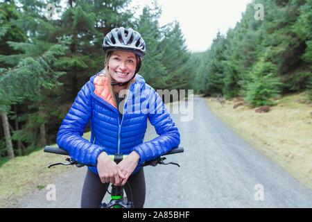 Portrait lächelnde Frau Mountainbiken auf Trail im Wald - Stockfoto