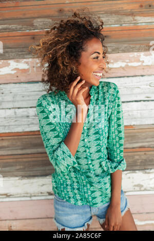 Portrait glückliche junge Frau gegen Laufbelag Wand - Stockfoto