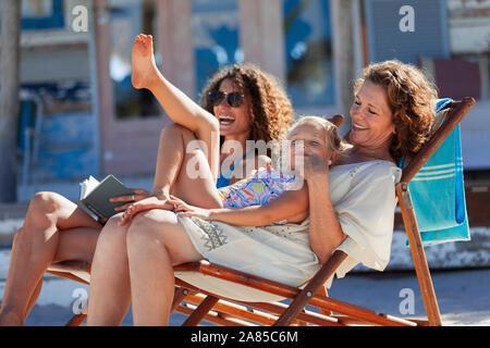 Verspielter, fröhlicher multi-Generation Frauen entspannen auf Sunny Beach - Stockfoto