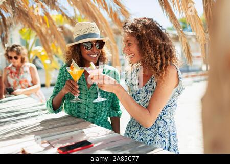 Glückliche junge Frauen Freunde trinken Cocktails auf Sunny Beach Bar - Stockfoto