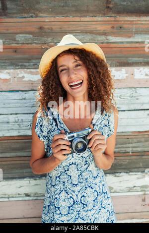 Portrait glückliche, unbeschwerte junge Frau mit retro Kamera gegen Laufbelag Wand - Stockfoto