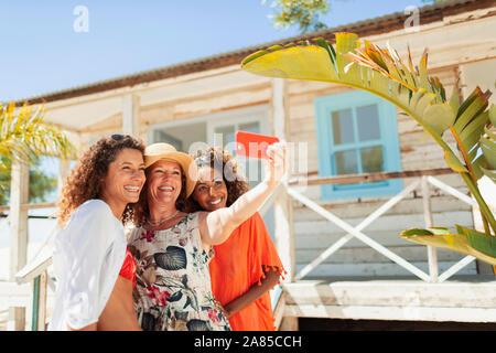 Glückliche Mutter und erwachsenen Töchtern unter selfie außerhalb Sunny Beach Hut - Stockfoto