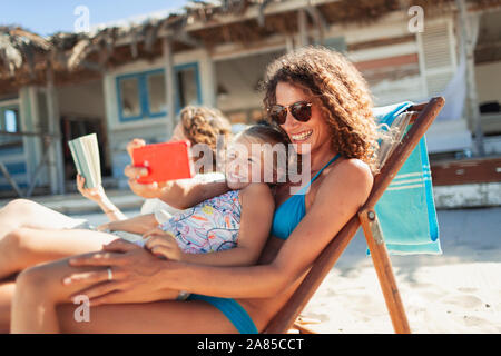 Glückliche Mutter und Tochter unter selfie mit Fotohandy auf Sunny Beach - Stockfoto