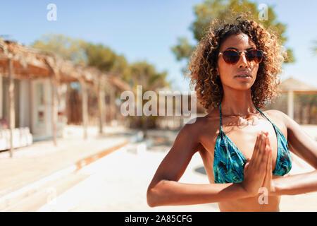 Portrait ruhige junge Frau im Bikini mit Yoga auf der sonnigen Terrasse - Stockfoto