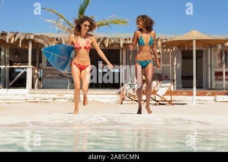 Unbeschwerte junge Frauen Freunde mit Surfbrett auf Sunny Beach - Stockfoto