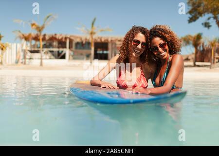 Portrait glückliche junge Frauen Freunde mit Surfbrett in sonnigen Ozean - Stockfoto