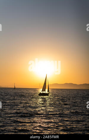 Segelboot auf der San Francisco Bay bei Sonnenuntergang mit Golden Gate Bridge Stockfoto