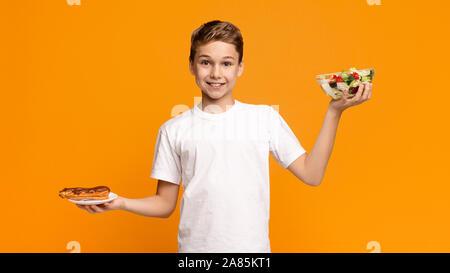 Teenager mit frischem Salat und Schokolade donut - Stockfoto