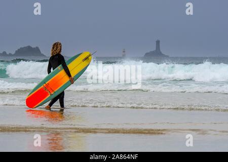 Leuchtturm La Vieille und Surfer mit Surfbrett am Strand zu Fuß ins Meer an der Pointe du Raz, Finistère, Bretagne, Frankreich - Stockfoto