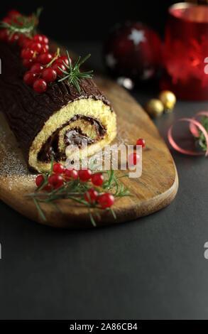 Schokolade Weihnachten Yule Log, Buche de Noel auf Holz Schneidebrett. Weihnachten Dekoration auf dunklem Hintergrund. Nahaufnahme - Stockfoto
