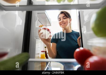 Glückliche Frau das Essen aus dem Kühlschrank zu Hause - Stockfoto