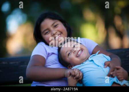 Kleiner Bruder genießen die Gesellschaft seiner Schwester wie er lacht mit einem freudigen Ausdruck und hält ihre Hand. - Stockfoto