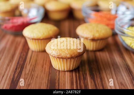 Drei mini Cupcakes mit Glas Schalen von rot, orange und gelb Streusel auf der Oberfläche des Holzes. - Stockfoto