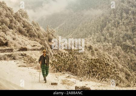 Ein reifes Alter (ein Mann der Nepalesischen Ethnizität) einsame Wanderer auf einem Wanderweg allein zu Fuß in einer schönen Winter Umgebung von North East Himalayan Mo