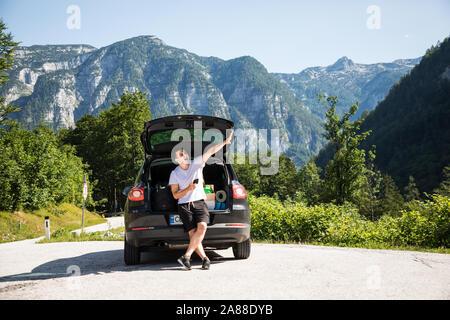 Junger Mann mit Telefon, während im Kofferraum sitzen und wies mit der Hand auf die Berge - Stockfoto