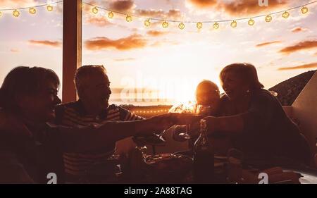 Gerne ältere Freunde jubeln und Toasten mit Rotwein auf der Terrasse Abendessen - reife Menschen Spaß zusammen auf der Dachterrasse speisen bei Sonnenuntergang - Stockfoto