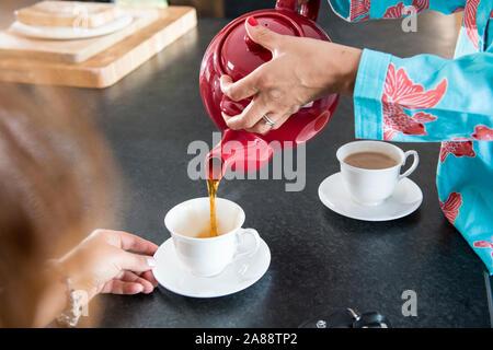 Tea time Gießen englischer Tee von Teekanne Tasse Tee - Stockfoto