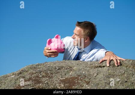 Lächelnd Geschäftsmann halten auf einen treuen rosa Sparschwein, wie er oben auf einem felsigen Klippe erreicht. - Stockfoto